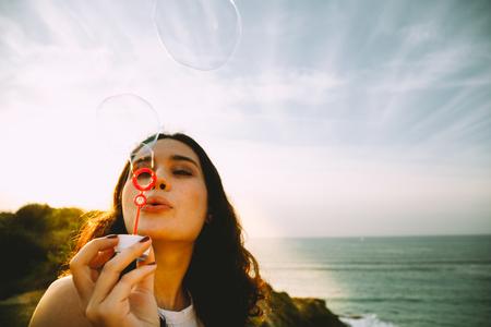 Jeune femme soufflant des bulles sur la mer au coucher du soleil Banque d'images - 73585661