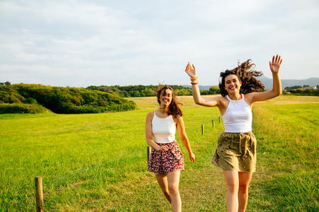Funny female friends jumping in a green field Stock Photo