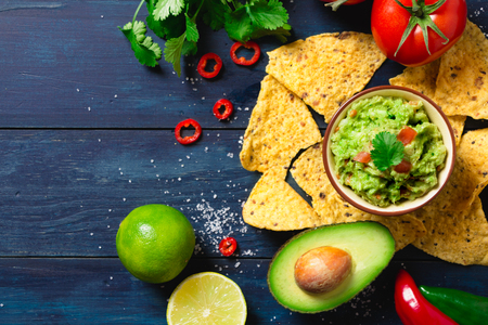 Guacamole bowl with ingredients and tortilla chips on a blue painted wooden table. Top view Stock Photo