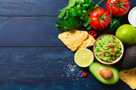 Guacamole bowl with ingredients and tortilla chips on a blue painted wooden table. Top view Banque d'images
