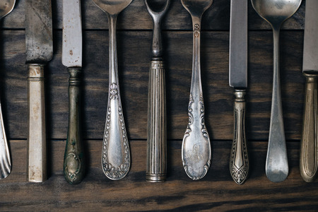 Old cutlery on a rustic wooden table. Top view