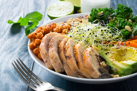 Buddha bowl with kale salad, quinoa, roasted chickpeas, grilled chicken breast, avocado, baked sweet potatoes, leek sprouted seeds, pine nuts, sesame and seeds. Dressing of yogurt sauce, olive oil, lime and mint Stock Photo