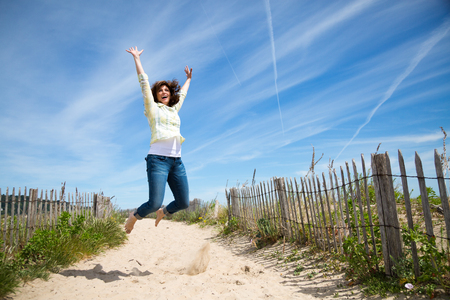 Happy middle aged woman jumping on the beach crazy for vacation