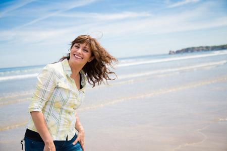 행복 한 중간 세 여자 해변에서 산책을 즐기고
