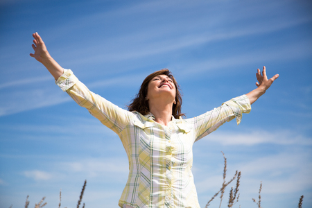 arms up: Attractive middle aged woman enjoying nature with arms raised to the blue sky Stock Photo