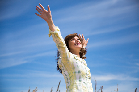 Attractive middle aged woman enjoying nature with arms raised to the blue sky 스톡 콘텐츠