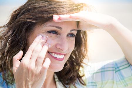 Beautiful middle aged woman applying sunscreen lotion on face on the beach Banque d'images