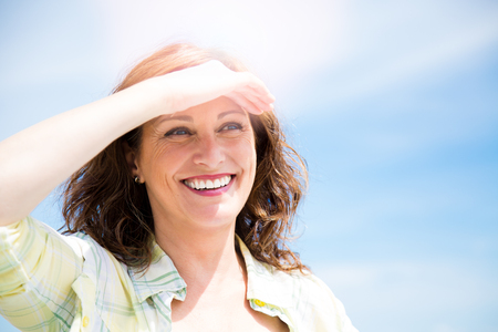 Happy beautiful middle aged woman protecting from sun with hand as a sun visor Stok Fotoğraf