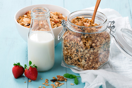 sunflower seeds: Homemade baked granola in a glass jar, a bottle of milk and strawberries on a turquoise wooden table. Healthy breakfast Stock Photo