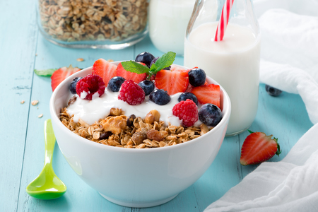 sunflower seeds: Healthy breakfast in a bowl with homemade baked granola, frozen berries, fresh strawberries and yogurt on a turquoise wooden table