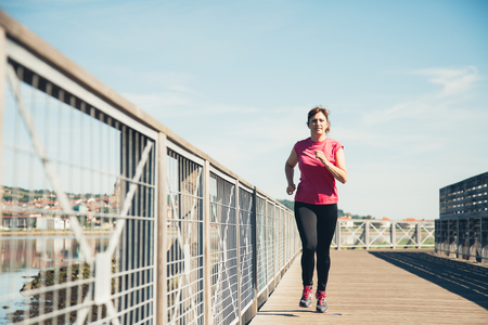 Middle aged woman running outdoors in a sunny and hot day Stock Photo