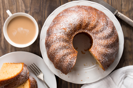 Slice of yogurt bundt cake served with a cup of coffee with milk. Top view Stock Photo - 80191139