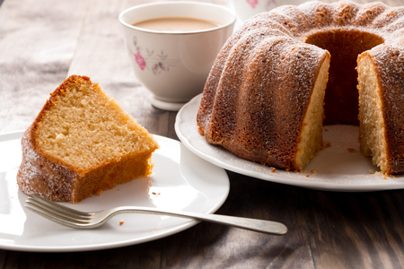 Slice of yogurt bundt cake served with a cup of coffee with milk