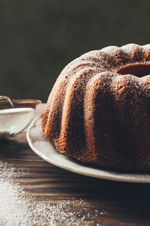 Bundt cake with icing sugar. Dark mood Stock Photo