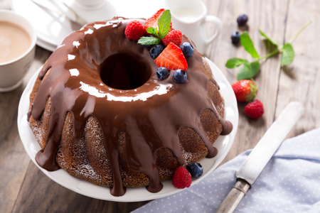 Chocolate bundt cake with melted chocolate and frozen berries