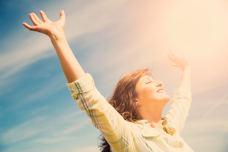Attractive middle aged woman enjoying the sun and nature with outstretched arms. Freedom concept.