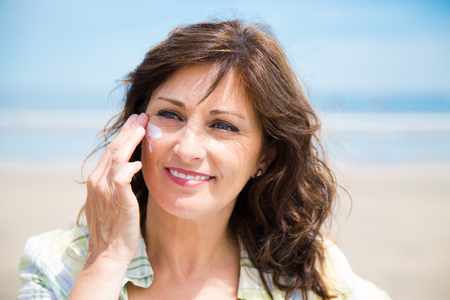 Beautiful middle aged woman applying sunscreen lotion on face on the beach Archivio Fotografico
