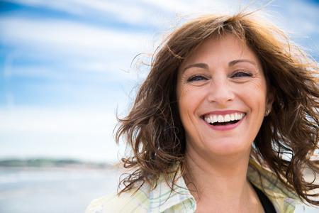 Feliz mujer de mediana edad con cabello desordenado riendo en la playa Foto de archivo - 81967333