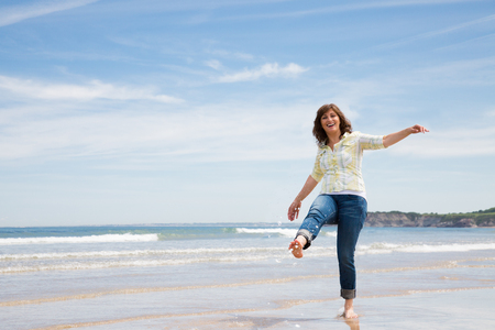 Beautiful and funny middle aged woman splashing water with foot on the seashore Stockfoto