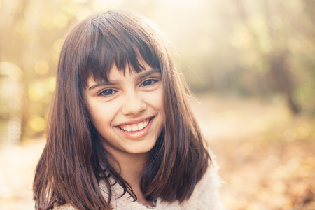 Portrait of a beautiful happy little girl outdoors in autumn Banco de Imagens