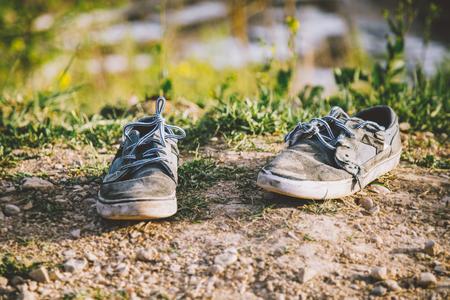 지상에 버려진 오래된 착용 된 회색 운동화 스톡 콘텐츠