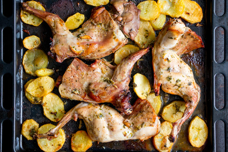 Roasted rabbit with potatoes and herbs on a oven tray. Top view Stock fotó