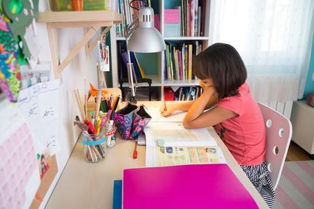 学校の女の子は彼女の机の中で自宅で宿題をして 写真素材
