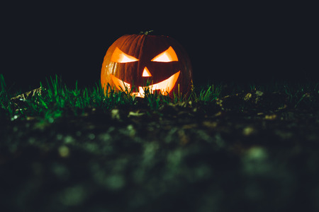 Halloween pumpkin on the grass at night