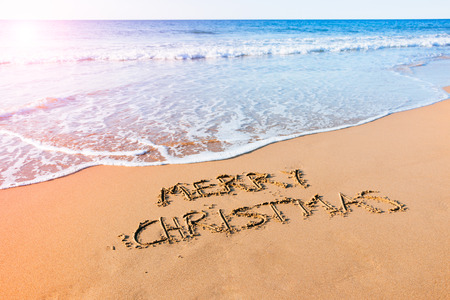 Merry Christmas written in the sand at the seashore on the beach