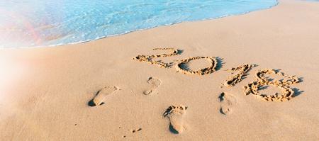 Year 2018 written on the sand at the seashore Stock Photo