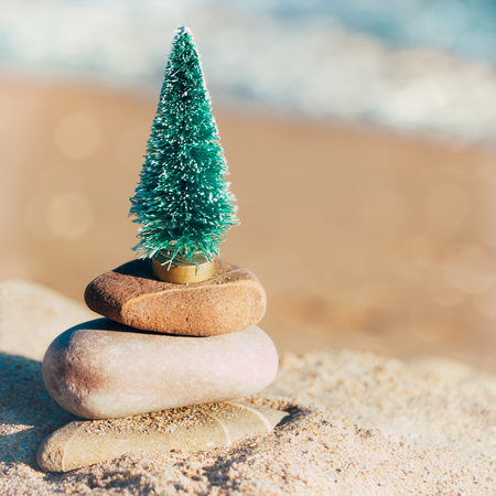 Miniature of a Christmas tree on a stone stack on the beach. Concept of relaxing Christmas vacation on the beach