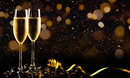 Dos copas de champán con confeti dorado, purpurina, serpentina y luces. Noche de concepto de celebración