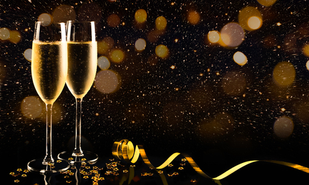 Two glasses of champagne with golden confetti, glitter, serpentine and lights. Night of celebration concept Foto de archivo