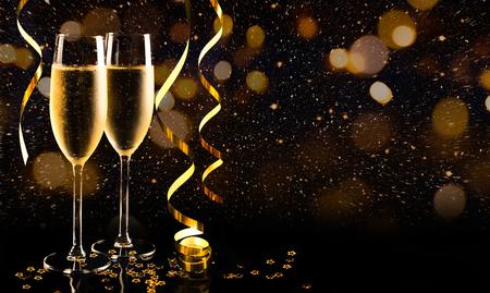Deux verres de champagne avec confettis, paillettes, serpentine et lumières d'or. Concept de nuit de fête Banque d'images