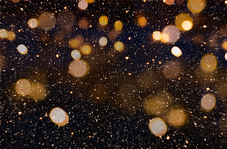 Christmas or New Year celebration background with golden glitter explosion and bokeh