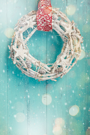 Natural wreath painted in white hanging on a aquamarine door with lights bokeh and snow