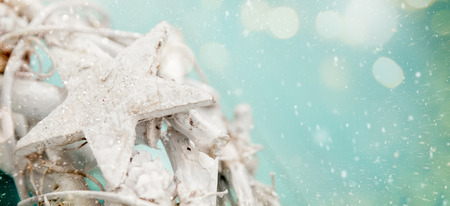 Detail of a star in a natural wreath painted in white on a aquamarine wooden background with lights bokeh, snow and sparks