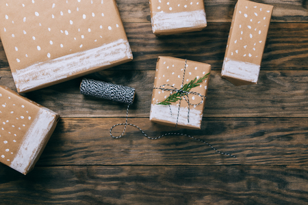 Christmas presents on brown paper decorated with painted snow and fir branches on a rustic wooden board. Top view