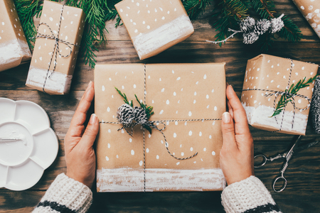 WomanÃ?´s mãos que envolvem presentes de Natal no papel marrom decorado com neve, ramos do abeto e pinecones pintados em uma placa de madeira rústica. Vista do topo