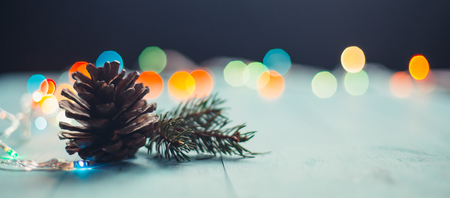 Pine cone and fir branch on blue wooden planks with lights bookeh at the background. Shallow depth of field Stock Photo