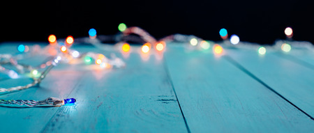 Colorful Christmas lights bokeh on blue wooden planks. Shallow depth of field Stock fotó