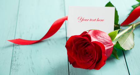 Red rose with a red ribbon on a aquamarine wood board with a card to customize. Valentines or anniversary background Zdjęcie Seryjne