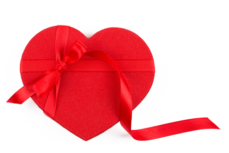 Red heart shaped gift box with a red bow isolated on white