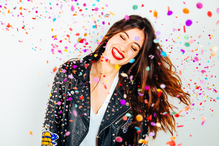 Happy young and beatiful woman with fashion leather jacket enjoying the party with confetti Фото со стока