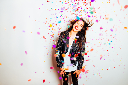 Happy young and beatiful woman with fashion leather jacket enjoying the party with confetti Standard-Bild