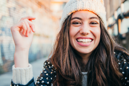 Portrait of a happy and beautiful young woman with woolen cap and lleather jacket laughing Banco de Imagens - 91116268