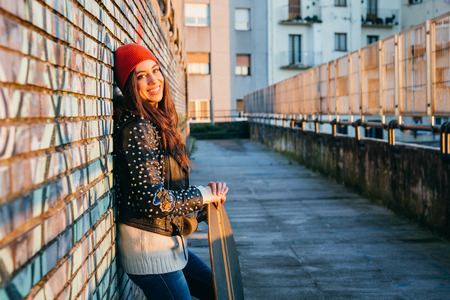 Young  and beautiful skater woman enjoying the sunset in the city resting on a brick wall with graffiti