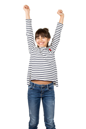 Little happy girl in striped t-shirt and blue jeans raising arms in sign of victory. Isolated on white