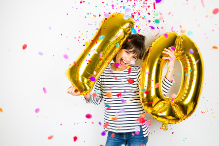 Happy little girl holding two golden balloons making the 10 number while falling confetti on white background. 10th anniversary celebration party.