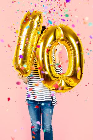 Niña que sostiene dos globos de oro que hacen el número 10 mientras que cae el confeti en un fondo rosado. Fiesta de celebración del 10 ° aniversario. Foto de archivo - 91614579